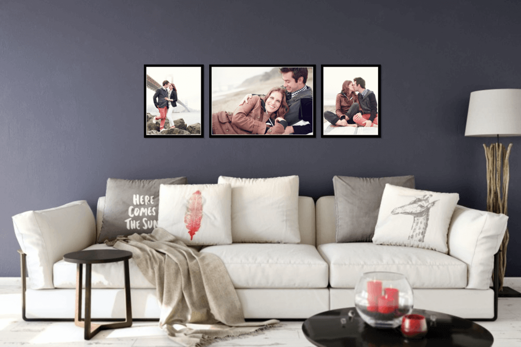 Framed gallery wall of engagement session in San Francisco designed in Swift Galleries on a dark wall over a trendy couch.