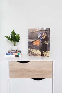 Wall art piece sitting on modern dresser with photo books